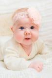 有胖的穿白色衣裳的面颊和大蓝眼睛的惊奇女婴和与说谎在床上的花的桃红色带 免版税库存图片