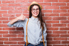 美丽的女孩画象显示好标志的便衣和帽子的 免版税库存照片