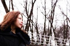 享受她的时间的美丽的女孩外面在冬天公园 免版税图库摄影