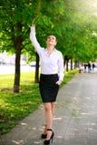 走在城市绿色公园的年轻和愉快的女商人 免版税库存照片