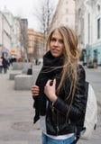 走与在欧洲街道上的一个背包的一个年轻美丽的白肤金发的女孩的画象  室外 温暖的颜色 免版税库存图片