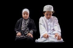 小年轻回教男孩和女孩在祷告期间 库存照片