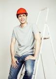 Молодой реальный человек труженика изолированный на белой предпосылке на представлять лестницы усмехаясь, концепция дела Стоковые Фото