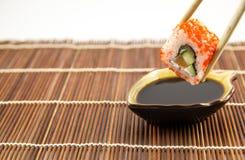 寿司卷用三文鱼黄瓜和乳酪与筷子 免版税库存照片