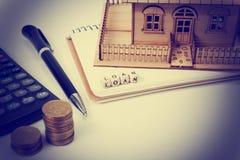 住房购买和保险的概念 办公桌桌有供应顶视图 计算器 金黄硬币,笔 库存图片