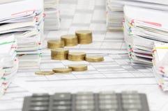 Τα χρυσά νομίσματα βημάτων έχουν τον υπολογιστή θαμπάδων μεταξύ του σωρού της γραφικής εργασίας Στοκ Εικόνες