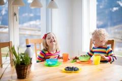 孩子食用早餐在晴朗的厨房 图库摄影