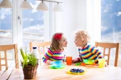 孩子食用早餐在晴朗的厨房 免版税库存图片
