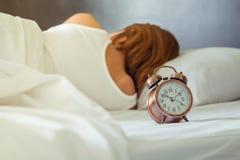 闹钟和年轻睡觉的妇女在床上 库存照片