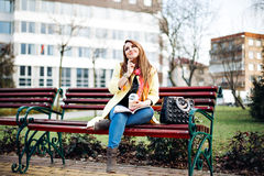 惊人的妇女坐在读杂志之外的一条长凳,听到音乐,饮用的可口咖啡 穿戴  免版税库存图片