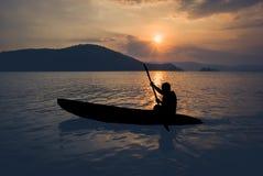荡桨在皮船的人剪影 免版税库存照片