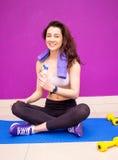 一名性感的妇女的画象在一种锻炼以后的与在她的拿着一个瓶水的肩膀的一块毛巾 库存图片