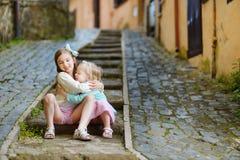 笑和拥抱的两个可爱的妹在温暖和晴朗的夏日 免版税库存照片