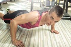 做在健身房的年轻人俯卧撑 免版税图库摄影