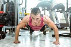 做在健身房的年轻人俯卧撑 免版税库存图片