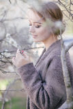 在树附近的年轻美丽的妇女在开花在春天 发型区域 免版税库存图片