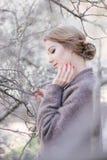 在树附近的年轻美丽的妇女在开花在春天 发型区域 免版税图库摄影