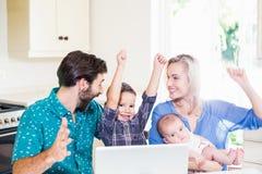 激动的父母和孩子使用膝上型计算机在厨房里 库存照片