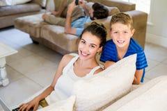 微笑的母亲和儿子画象坐沙发 库存图片