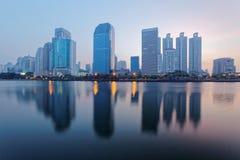 曼谷美好的城市地平线在与湖边摩天大楼和反射的黎明 库存图片