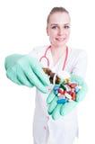 拿着一个瓶子药片和胶囊的美丽的微笑的医生 免版税库存照片