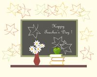 深灰黑板与白色字法愉快的老师天,有白花的红色花瓶,在书的绿色苹果计算机 免版税库存图片