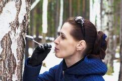 妇女饮用的桦树树汁 免版税库存图片