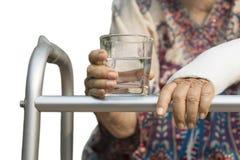 资深妇女使用步行者的被伤的腕子在后院 免版税图库摄影