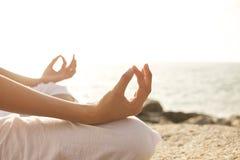 在瑜伽姿势的少妇凝思在热带海滩 免版税图库摄影