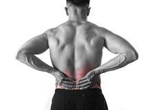 握疼痛低后腰部的年轻强健的身体体育人遭受在运动员重音的痛苦 免版税图库摄影