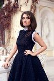 摆在短的黑礼服的年轻美丽的时髦的女孩 库存照片
