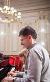 钢琴演奏者和他的小女孩学生在教训期间 免版税库存照片