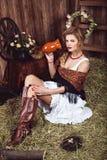 秸杆的年轻白肤金发的妇女在土气样式 免版税库存照片