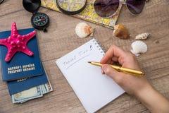 η γυναίκα γράφει στο κενό σημειωματάριο, εργαλεία ταξιδιού Στοκ Φωτογραφίες