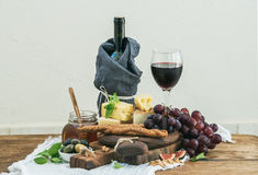 杯红葡萄酒、乳酪板、葡萄、无花果、草莓、蜂蜜和面包条在土气木桌,光上 免版税图库摄影