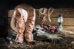 Натюрморт с ковбойской шляпой и традиционными кожаными ботинками Стоковое Изображение