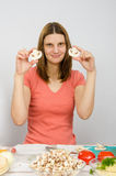 坐在厨房用桌上和拿着蘑菇的女孩切成了两半 免版税库存照片