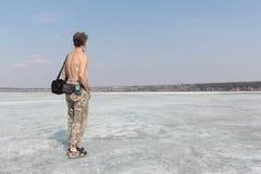 有站立在河的冰的赤裸躯干的灰发的人 免版税库存照片