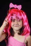 Όμορφο μικρό κορίτσι που φορά μια ρόδινη τοποθέτηση περουκών σε έναν θάλαμο φωτογραφιών για ένα κόμμα Στοκ Φωτογραφία