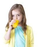 喝橙汁的儿童女孩隔绝在白色 免版税库存照片