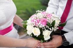 拿着花束的新郎和新娘特写镜头射击  免版税库存图片