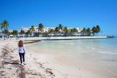 在晴朗的南海滩的女孩步行在大西洋附近的基韦斯特岛 库存图片