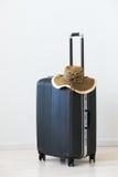 在木背景的大行李和柳条帽子 免版税库存图片