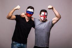 俄罗斯对灰色背景的英国 国家队的足球迷庆祝,跳舞并且尖叫 库存图片