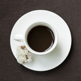 咖啡与白花的在一张棕色桌布 库存图片