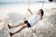 女孩坐在热带海滩的摇摆,天堂海岛 免版税库存照片