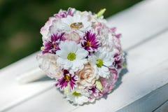 Δύο χρυσά γαμήλια δαχτυλίδια στο ελατήριο ανθίζουν την ανθοδέσμη Στοκ φωτογραφία με δικαίωμα ελεύθερης χρήσης