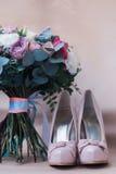 Όμορφα γαμήλια παπούτσια με τα υψηλά τακούνια και μια ανθοδέσμη των ζωηρόχρωμων λουλουδιών Στοκ Φωτογραφίες
