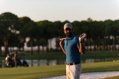 在高尔夫球场的高尔夫球运动员画象日落的 库存图片