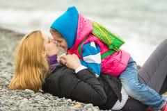 说谎在有卵石花纹的海滨的年轻母亲亲吻鼻子她的女儿坐她的骑马 免版税库存图片